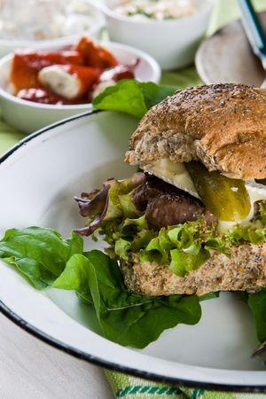 beefburger: Juicy beefburger in a fresh bread bun with salad Stock Photo