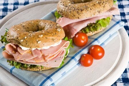 Two fresh bagels with honey roasted ham and cream cheese on blue napkin Stock Photo - 3682897