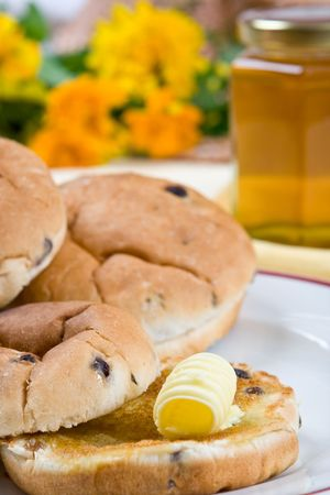 calorie rich food: Tea cakes with melting butter on a plate (flowers and honey in the background)