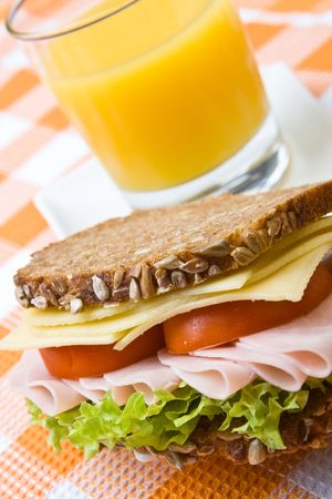 Fresh wholemeal cheese and ham sandwich with orange juice photo