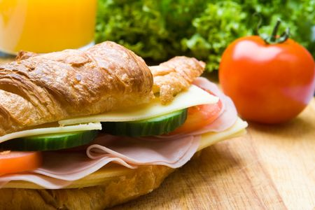 Fresh croissant with ham, cheese and salad on a wooden board