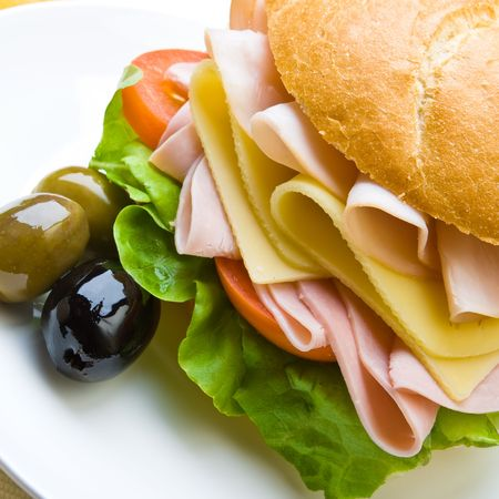 Delicious ham, cheese and salad sandwich with olives Imagens
