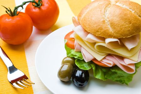 Delicious ham, cheese and salad sandwich with olives photo