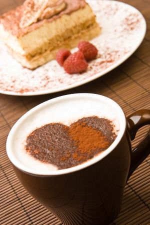 Cappuccino with a chocolate heart and a slice of tiramisu photo