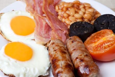 comida inglesa: Ingl�s tradicional desayuno - los huevos, salchichas, frijoles, tocino y el pud�n negro Foto de archivo