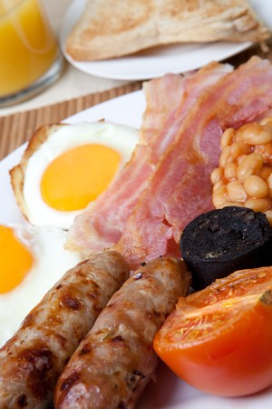 Traditional english breakfast - egg, sausages, beans, bacon and black pudding with toast photo