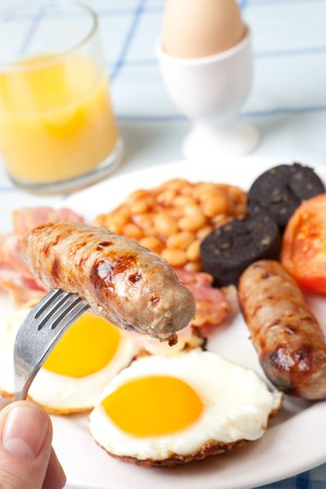 Traditional english breakfast - egg, sausages, beans, bacon and black pudding with orange juice photo