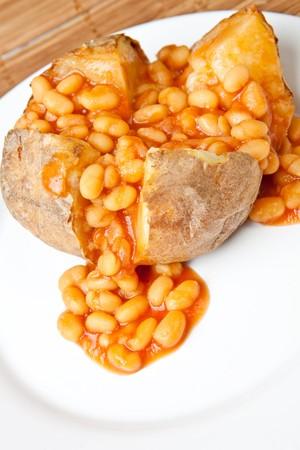 jacket potato: Hot and crispy baked potato stuffed with baked beans Stock Photo