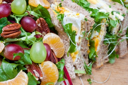 Healthy egg sandwich with salad and walnuts (focus on fruit) photo