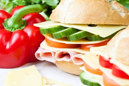 Delicious ham, cheese and salad sandwich on a wooden board photo