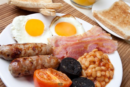 Traditional english breakfast - egg, sausages, beans, bacon and black pudding with toast