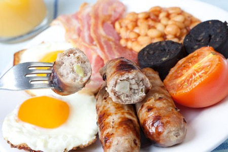 british cuisine: Traditional english breakfast - egg, sausages, beans, bacon and black pudding with toast