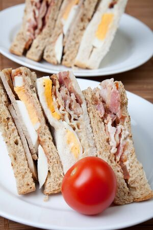 Bacon, egg and sausage sandwiches with a fresh tomato photo
