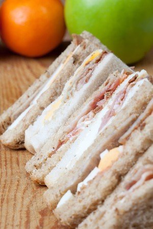 Bacon, egg and sausage sandwiches with an apple and an orange photo