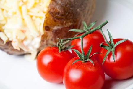 Hot and crispy baked potato stuffed with cheddar cheese, coleslaw and tomatoes photo