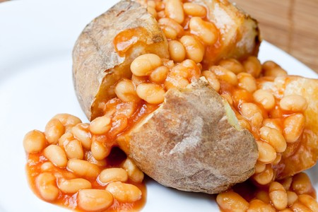 oven potatoes: Hot and crispy baked potato stuffed with baked beans Stock Photo