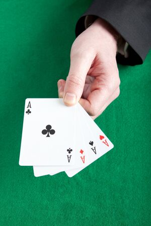card player: Card player holding all four aces on a green cloth Stock Photo