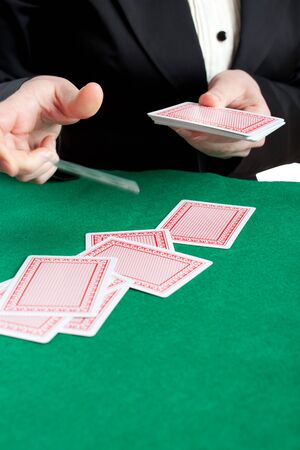 croupier: Croupier dealing playing cards with one card in the air