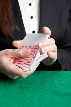 croupier: Croupier shuffling cards with motion blur top of the pack Editorial
