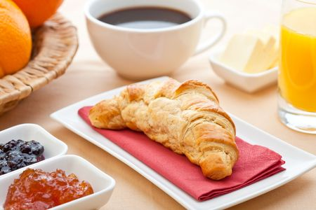 Continental breakfast with croissant, jam, coffee and orange juice photo