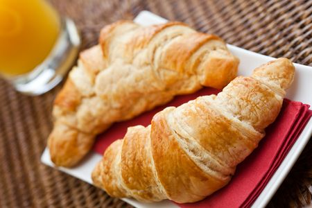 Continental breakfast with two croissants and a glass of orange juice photo