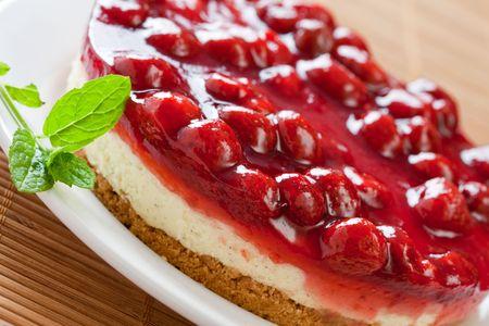 trozo de pastel: Deliciosa tarta de queso con fresa menta fresca en un plato blanco