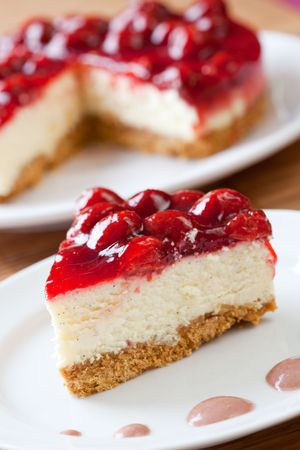 Slice of delicious strawberry cheese cake with a cake in the background Imagens