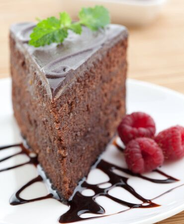 Slice of delicious chocolate cake with raspberries and mint photo