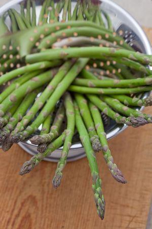 a colander: Fresh asparagus in a colander Stock Photo