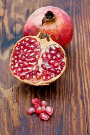 punica granatum: Fresh pomegranates on a wooden board