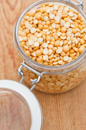 Yellow split lentils in a glass jar on a wooden background photo