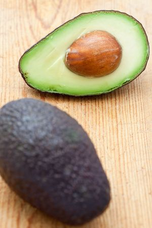 Half an avocado with stone on a wooden board Imagens