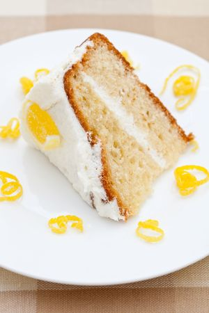 Slice of delicious lemon sponge cake with lemon rind on a white plate photo