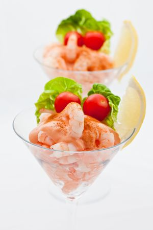 Two prawn cocktail appetizers with small tomatoes and fresh lemon Imagens