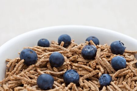 Bran breakfast cereal with blueberries in a dish photo