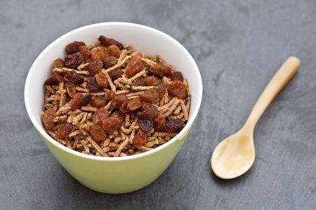 Bran breakfast cereal with sultanas in a green bowl photo