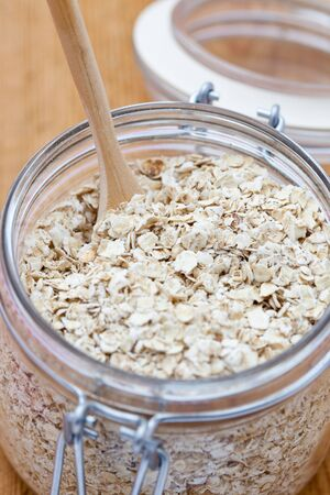 Porridge oats in a glass jar with a wooden spoon photo
