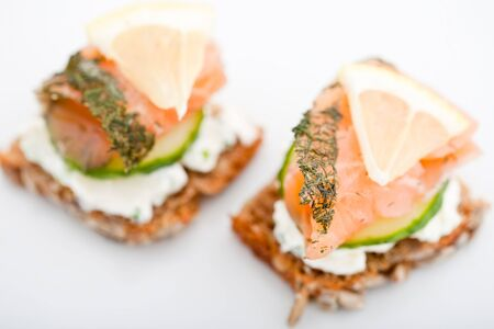 Two smoked salmon canapes on brown bread with cream cheese and cucumber Imagens