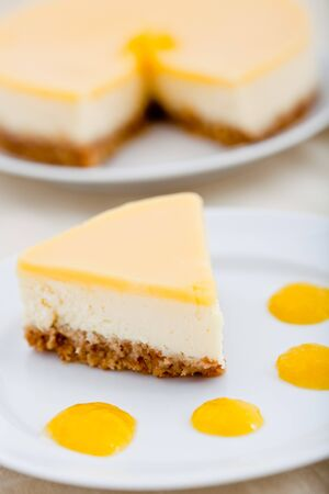 Slice of delicious lemon cheesecake with a cake in the background. Shallow DOF