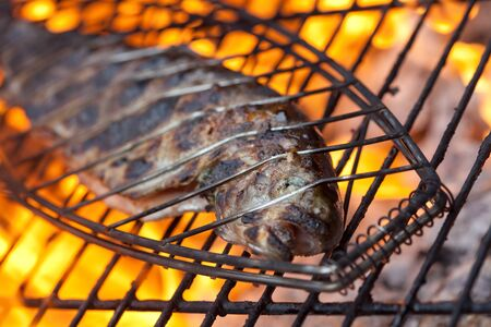 Trout cooking on a BBQ Imagens