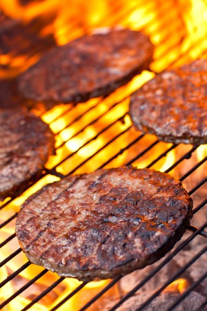 Large flame grilled beefburgers on a BBQ