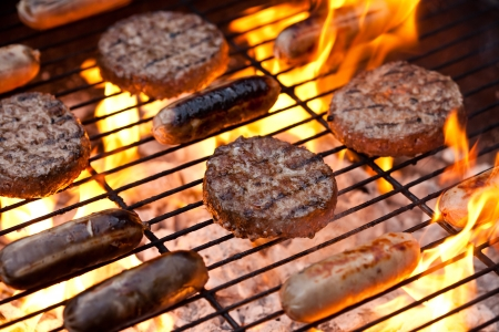 Flame grilled sausages and beefburgers on a BBQ