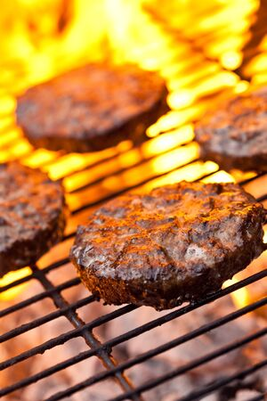 Flame grilled beefburgers on a BBQ