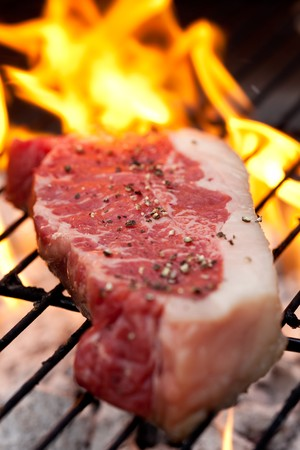 Raw steak with peper on the barbecue
