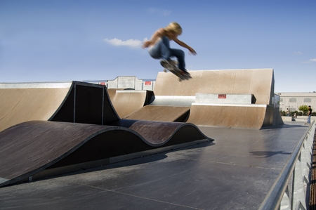 Skater doing a big air ollie in a skate park photo