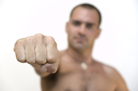 aggressiveness: barechested man, close up and focus on his fist,