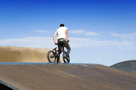Young man on a bmx bicycle on top of a ramp Stock Photo
