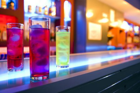 Three cocktail drinks on a bar, blurry color background Stock Photo