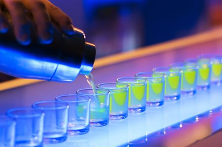 bar ware: Shot glasses being poured on a bar Stock Photo