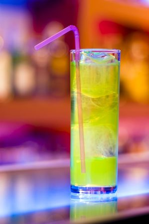Cocktail on a bar with colorful blurry background